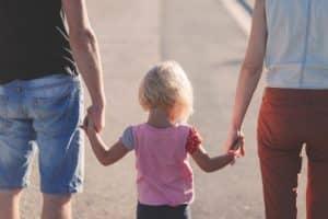Paar mit Kind in den Händen nachdem sie nach der Trennung wieder zusammen gefunden haben